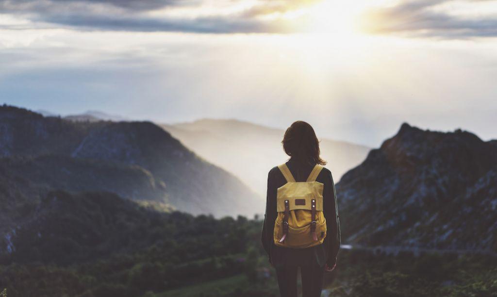 Děvče sbatůžkem kouká do dáli na hory,