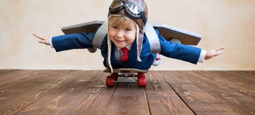Chlapeček v obleku napodobuje letadlo.